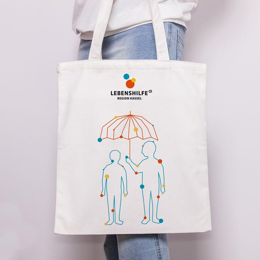 Lebenshilfe Kassel Jutebeutel mit Illustration. Zwei Menschen stehen nebeneinander. Ein Mensch hält Schirm zum Schutz über beide Personen.